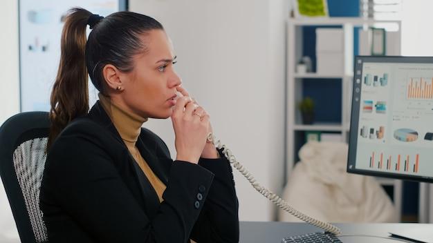 Многозадачный исполнительный менеджер разговаривает по стационарному телефону, объясняя графики компании удаленному коллеге