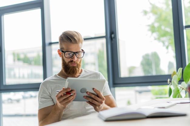 マルチタスク。眼鏡をかけて、オフィスのソファに座ってタッチパッドで作業しているハンサムな若い男