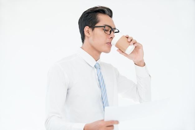 Multitasking man drinking coffee and using phone