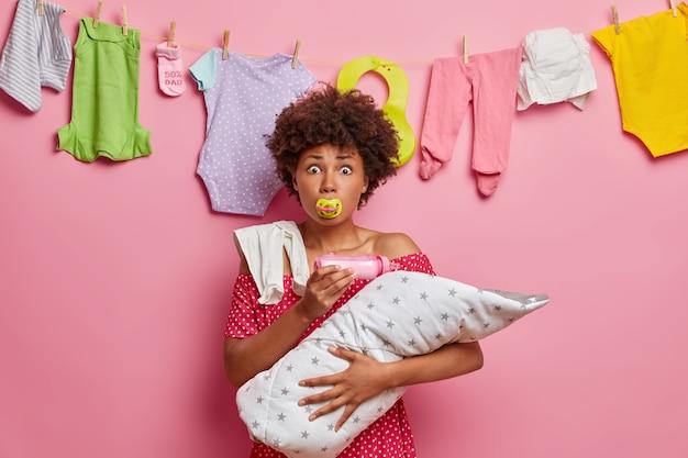 La madre multitasking nutre il neonato con il latte, succhia il capezzolo, tiene il neonato avvolto nella coperta, si prende cura del bambino piccolo, ha un'espressione scioccata e preoccupata quando sente cattive notizie. genitorialità, genitorialità