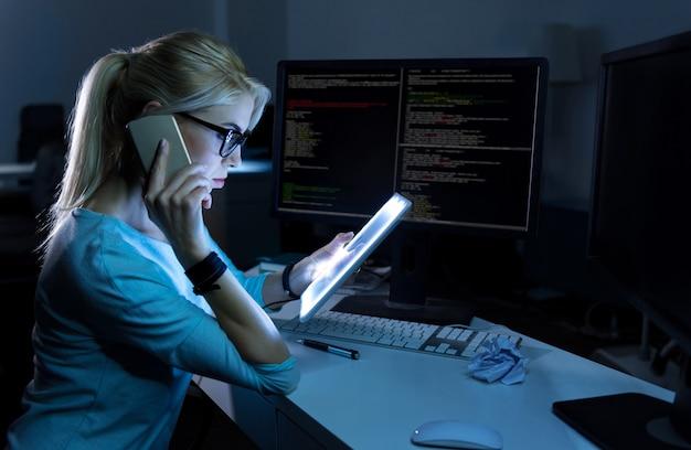멀티 태스킹 사람. 사무실에 앉아서 현대적인 기기를 사용하면서 집중력을 표현하고 전화로 이야기하는 매력적인 숙련 된 영재 안내 원