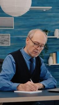 Uomo in pensione multitasking che legge sul laptop e scrive sul notebook che lavora da casa