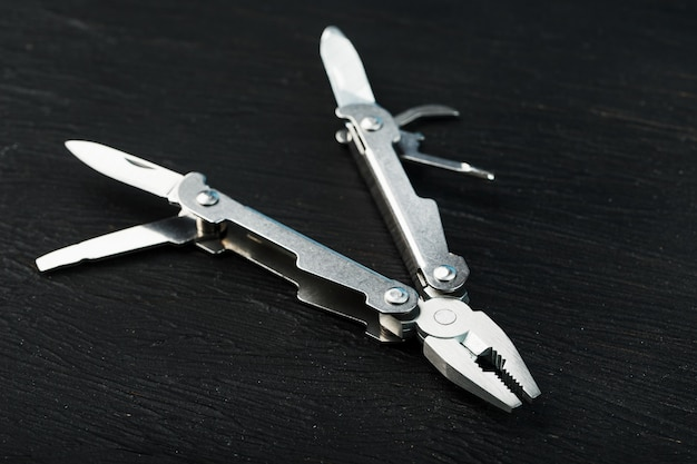 Multitool is a multi-functional tool on a black background. the concept of an expanded multi-tool with free space.