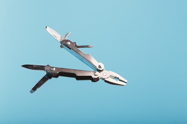 Multitool multi-function tool hovers on a blue background. the concept of an expanded multi-tool with free space.