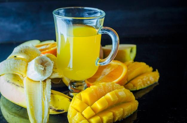 テーブルの上のフルーツのミディアムバラエティカップのマルチビタミンとマルチフルーツジュース