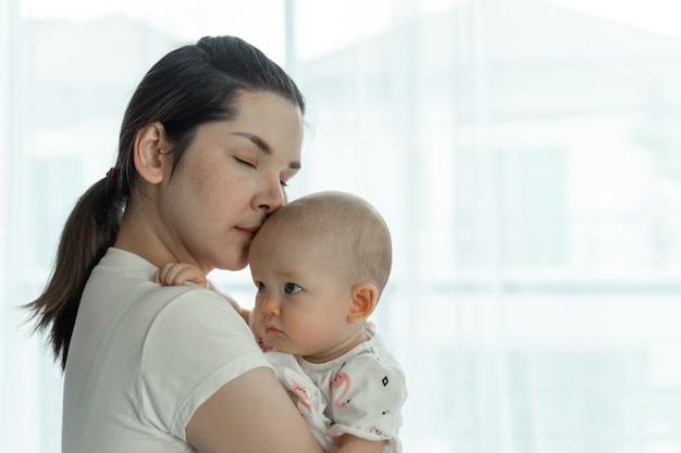 ママと赤ちゃんは白い部屋で喜んでお互いをからかいます
