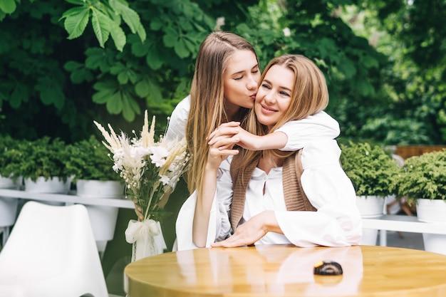 ママと女の子が笑顔でカフェで抱き締める