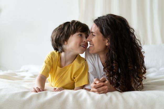 엄마와 아들은 침대에 누워 행복한 사랑을 나누는 엄마와 어린 아이가 주말에 함께 아침을 즐깁니다.
