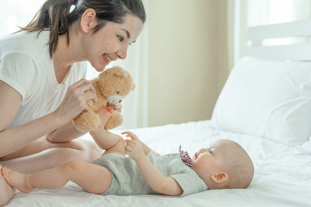 Mum and baby happily tease each other on a white bed.