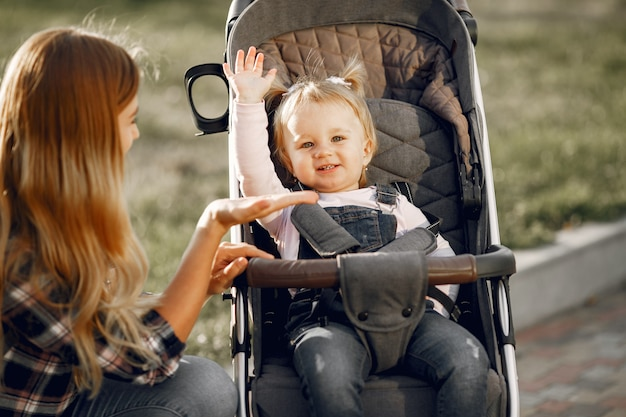 Mamma sulla strada della città. donna con il suo bambino seduto in una carrozzina. concetto di famiglia.