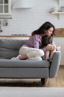 家族の喧嘩を気遣う母親の慰めが小さな男の子を強調した後、泣いている落ち込んでいる息子を慰める母親