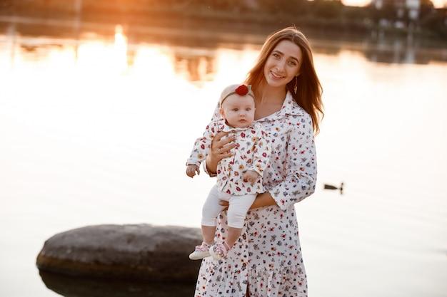ママ、屋外の小さな娘。女の赤ちゃんを持つ若い母親は、夕日の湖の近くのビーチの上を歩きます。池の家族の休日。自然の中で一緒に子供と肖像画のお母さん。