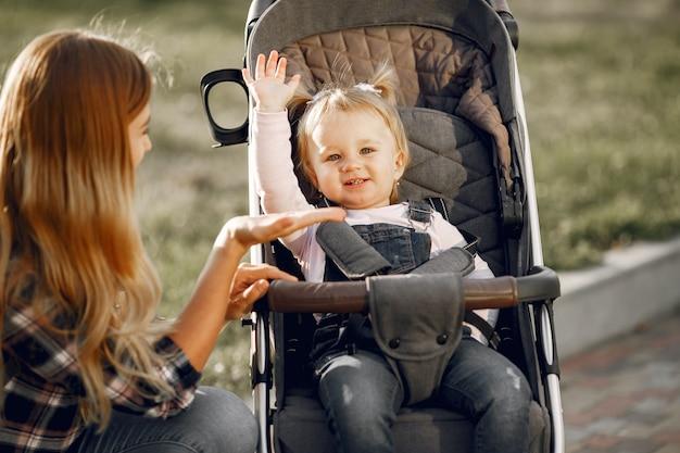 街の通りのお母さん。乳母車に座っている彼女の幼児を持つ女性。家族の概念。