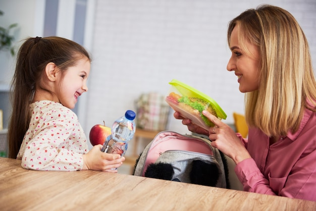 Mum putting lunch box with healthy food in backpack