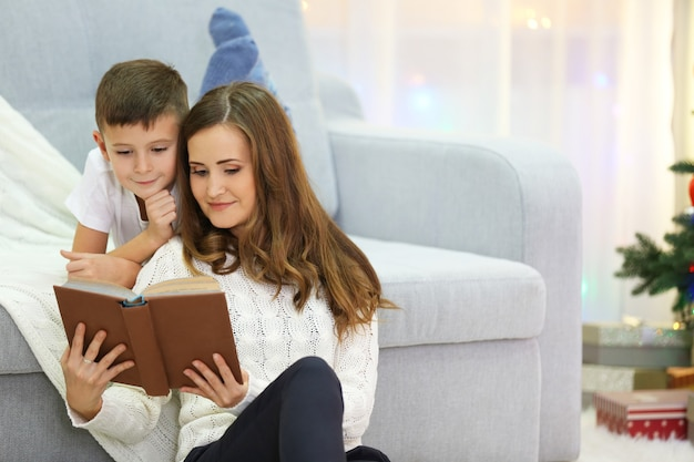 Mum reading book to son in christmas living room