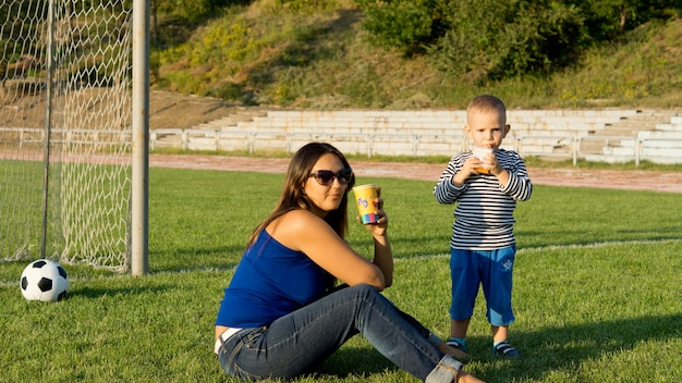 Mum and son playing soccer take a moments break to enjoy refreshment in front of the goalposts