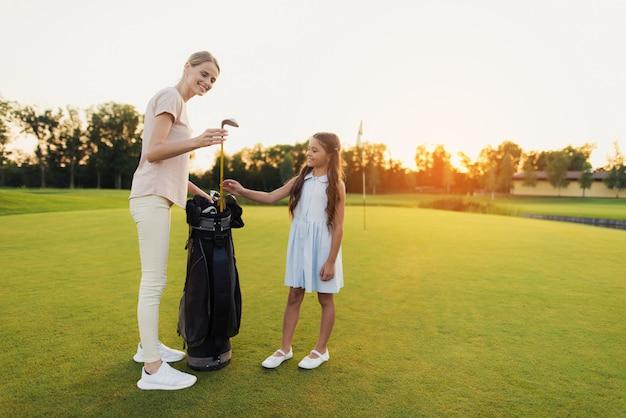 Mum takes a club teaches kid to golf family hobby.