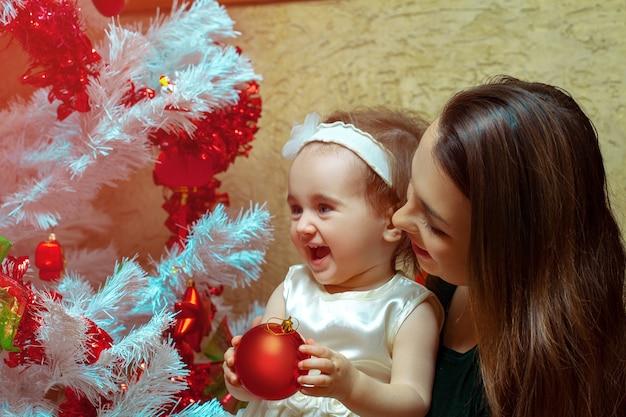 小さな娘と一緒のお母さんがクリスマスツリーを飾って楽しんでいます