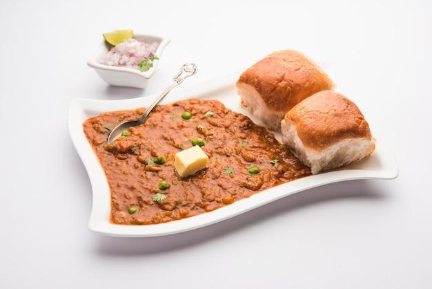 ムンバイスタイルのpavbhajiは、インドのファーストフード料理で、厚い野菜のカレーに柔らかいロールパンを添えて皿に盛り付けたものです。