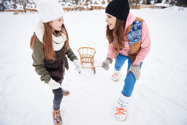 Mummy and daughter pulling sled together