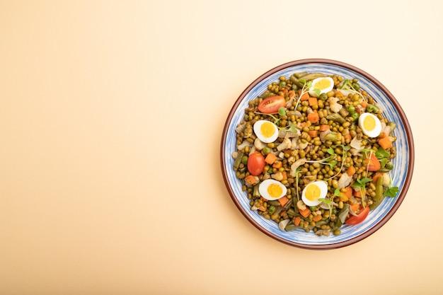 Каша из фасоли мунг с перепелиными яйцами, помидорами и ростками микрозелени на пастельно-оранжевом фоне.