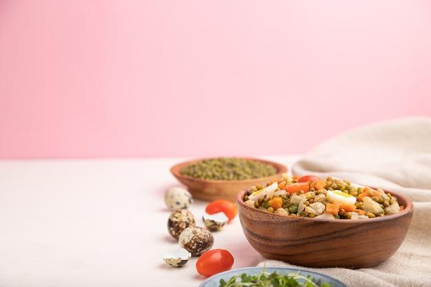 Каша из бобов мунг с перепелиными яйцами, помидорами и ростками микрозелени на белом и розовом фоне и льняной ткани.