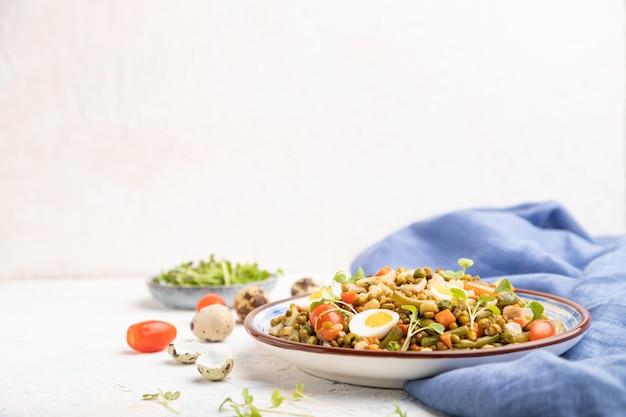 Каша из бобов мунг с перепелиными яйцами, помидорами и ростками микрозелени на белом фоне бетона и синей ткани.