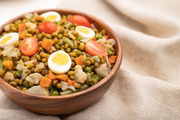 메추라기 알, 토마토 및 흰색 나무 테이블과 리넨 섬유에 microgreen 콩나물과 녹두 죽. 측면보기를 닫습니다.