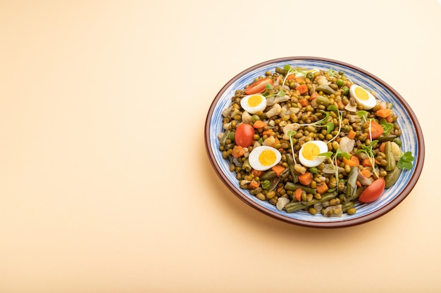 Mung bean porridge with quail eggs, tomatoes and microgreen sprouts on a pastel orange background.