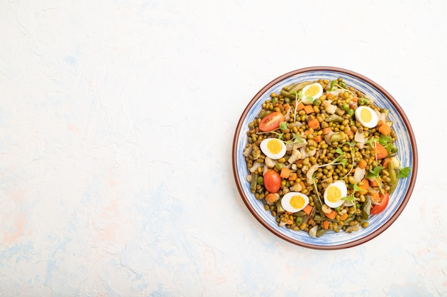 Mung bean porridge with quail eggs, tomatoes and microgreen sprouts on a white concrete background.