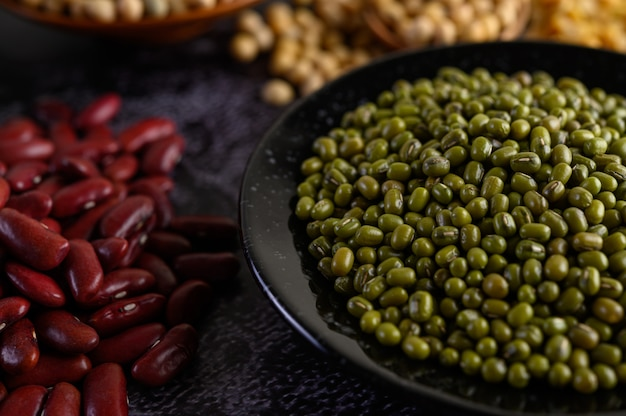 Mung bean and red bean on a black cement floor.