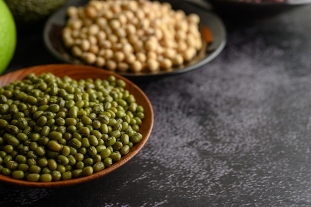 Mung bean and soy bean on the plate on a black cement floor surface.