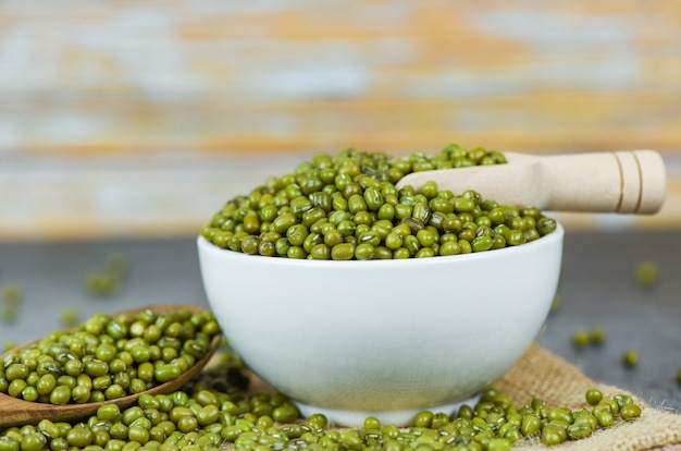 Mung beans on bowl agricultural products on the sack - dry green mung beans