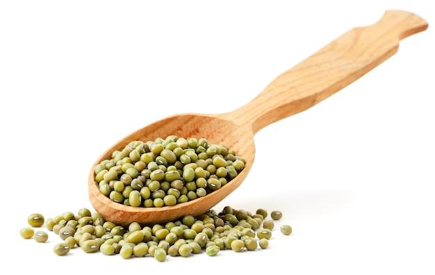 木のスプーンで緑豆と白い背景に振りかけた。孤立