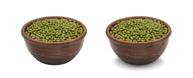 白い背景の上のシンプルな粘土ボウルの緑豆、孤立した影付き