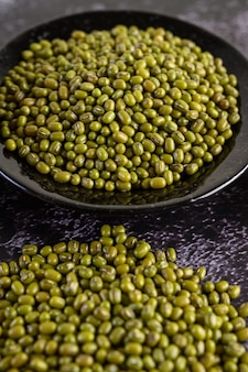 Mung beans on the plateon the black cement floor.
