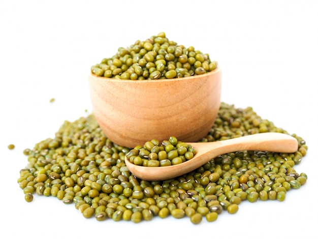 Mung beans in wooden bowl isolated on white surface