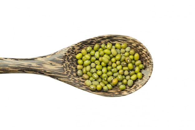 Mung beans over wooden spoon isolated on white
