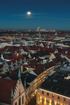 Город мюнхен на фоне заката. вид с воздуха на старый город мюнхена с горизонтом или городской пейзаж и главный собор во время рождества после зимнего закатного неба.