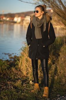 뮌헨, 독일-2020 년 11 월 22 일 : 뮌헨 근처 암 메르 제 호수에서 일몰을 즐기는 젊은 여성의 초상