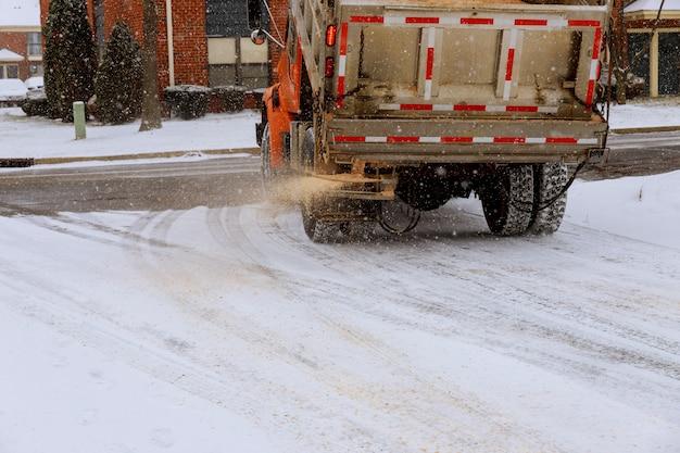 雪の道で塩分と砂の半分を振りかける市営車