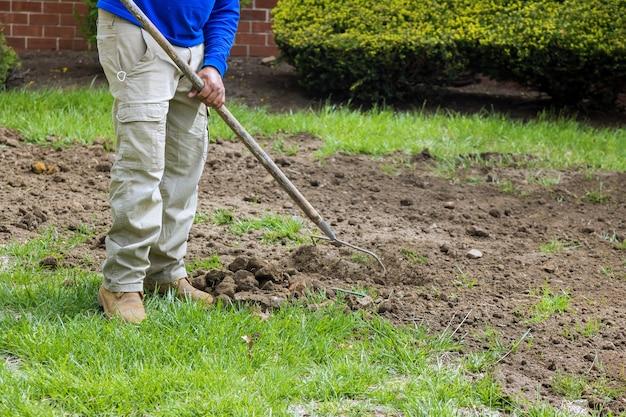 정원에서 활동적인 마지막 작업에 금속 갈퀴가 있는 시립 서비스 작업자 정원사