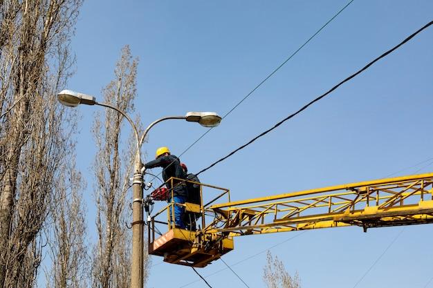 헬멧과 안전 보호 장비를 갖춘 도시 근로자가 가로등에 전선을 설치합니다.