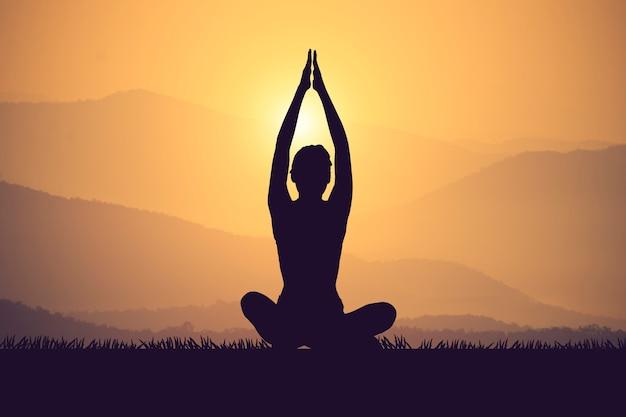 日没時にmuontainにヨガを練習するシルエットの若い女性。