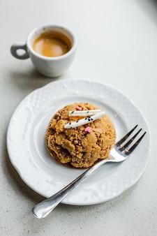 白いプレート、デザートフォーク、エスプレッソコーヒーのカップに伝統的なロシアのソビエトケーキmuraveynikまたはじょうごケーキ