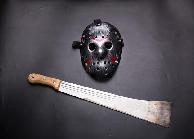 Хоккейная маска убийцы и мачете, изолированные на черном