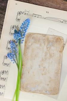ムスカリブルーの生花とコピースペース付きの古紙ノート