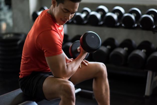 Ftiness 체육관 선반 근처에 무거운 아령으로 근육 아시아 웃는 남자 운동 팔뚝