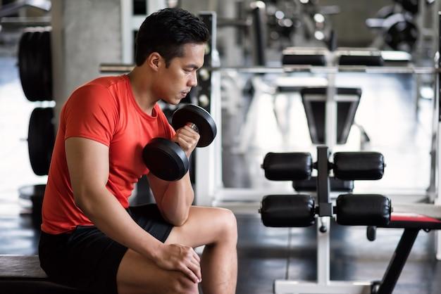 피트니스 체육관에서 의자에 무거운 아령으로 근육 아시아 젊은이 운동 bicep
