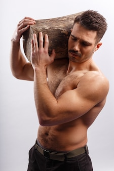 Muscle, athlete, sexy, hot, fit brutal bearded man with haircut, with naked torso, holding a tree trunk on his shoulders, over white background.